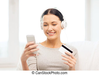 woman with smartphone and headphones at home - home, ...