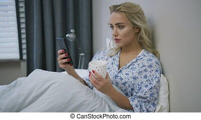 Woman with smartphone and mug on bed