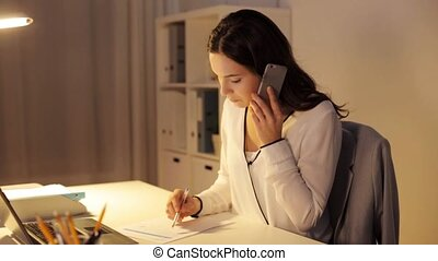woman with smartphone and papers at night office
