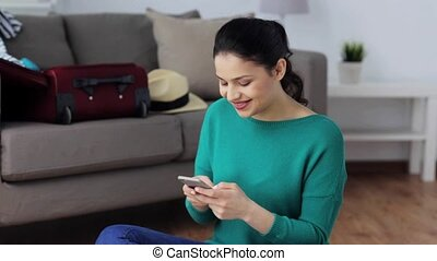 woman with smartphone at home going to travel