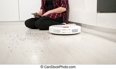 Woman with smartphone controls robot vacuum cleaner at home
