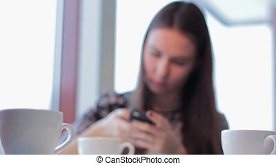 Woman with smartphone drinking cafe latte in cafe