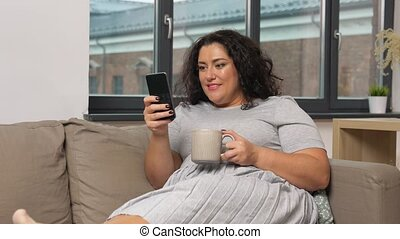 woman with smartphone drinking coffee at home - technology, ...