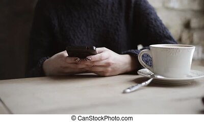 woman with smartphone drinking coffee in cafe