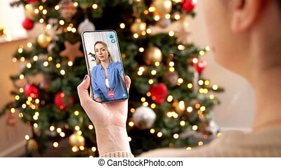 woman with smartphone has video call on christmas