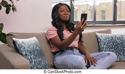 woman with smartphone having video call at home