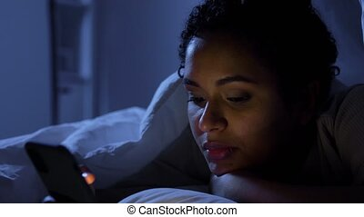 technology, internet, communication and people concept - young african american woman with smartphone lying in bed at home at night