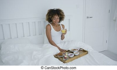 Woman with smartphone in bed having meal