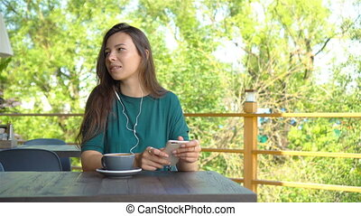 Woman with smartphone in cafe drinking coffee smiling and texting on mobile phone. Portrait of beautiful young girl