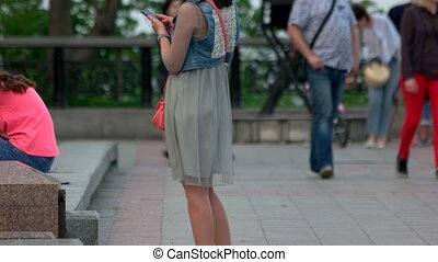 Woman with smartphone in crowded park.