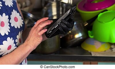 Woman with smartphone in the kitchen