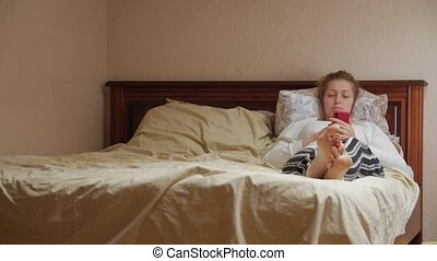 Woman With Smartphone Lying In Bed