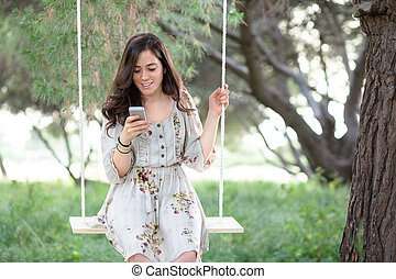 Woman with Smartphone on a Swing