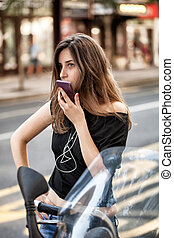 woman with smartphone on motorbike