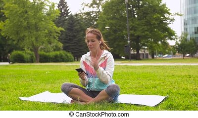 woman with smartphone putting music for meditation -...