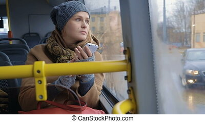 Woman with Smartphone Riding a Bus - Slow motion shot of a...
