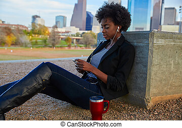 Woman with smartphone sitting in the park