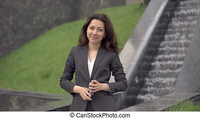Woman with smartphone standing and smiling