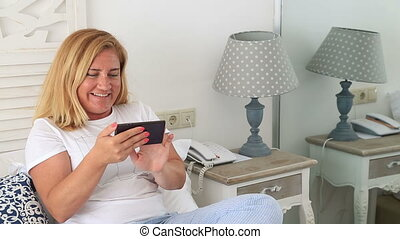 Woman with smartphone texting at home