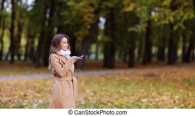woman with smartphone walking in autumn park - season,...