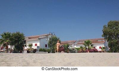 Woman with smile in red bikini promenade on beach