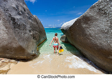 Young woman with snorkeling equipment at tropical beach among granite boulders at Virgin Gorda, British Virgin Islands, Caribbean