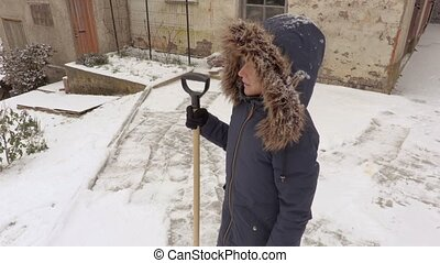 Woman with snow shovel before working