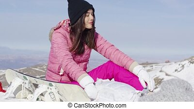 Woman with snowboard relaxing on mountain
