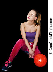 Woman with soccer ball isolated on black background