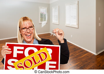 Woman with Sold For Sale Real Estate Sign and Keys In Empty Room of New House