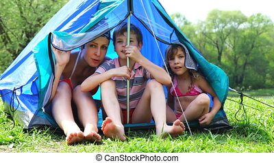 Woman with son and daughter sit talking in tent at forest