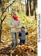 woman with  son gardening   in autumn