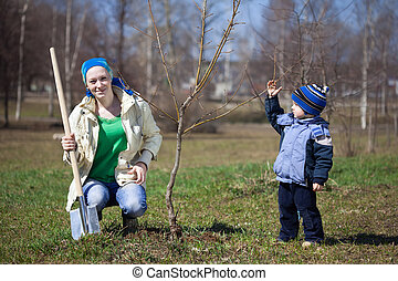 woman with son planting tree outdoor