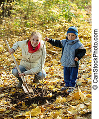 woman with son resetting tree in autumn - young woman with ...