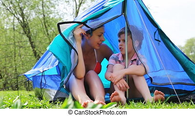 Woman with son sit talking, behind daughter in tent at forest