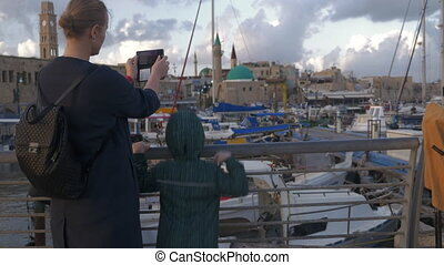 Woman with son taking photos when visiting Acre port, Israel...