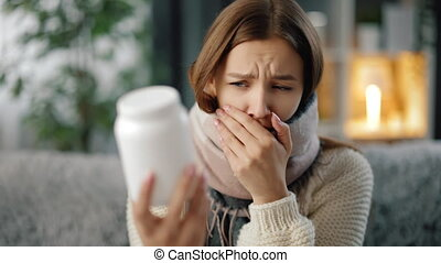 Woman with sore throat taking pills at home