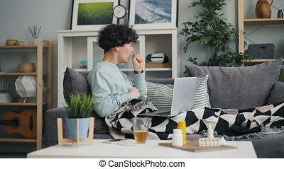 Woman with sore throat using laptop looking for information...