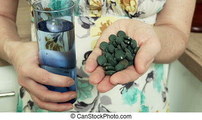 Woman with spirulina pills and glass of water.Healthy Lifestyles concept