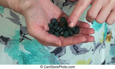 Woman with spirulina pills in hand.Healthy Lifestyles concept