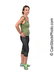 woman with sportswear on white background, hand on hip