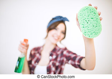 Woman with spray bottle and sponge - Young attractive woman...