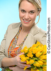Woman with spring flowers yellow tulips