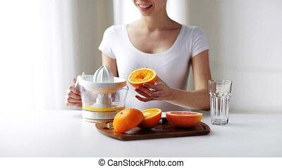 woman with squeezer squeezing orange juice at home - healthy...
