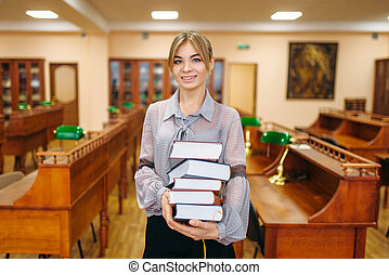 Woman with stack of books in university library