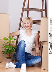 Woman With Stacked Cardboard Boxes Sitting On Floor