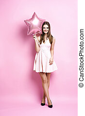 Woman with star shape balloon on pink background