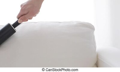 woman with sticky roller cleaning sofa upholstery