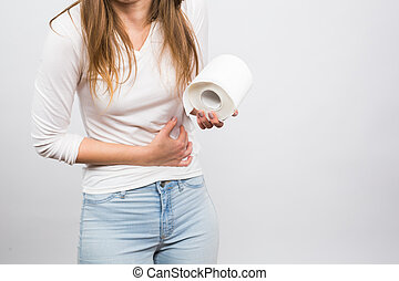 Woman with stomach pain and toilet paper roll on white background