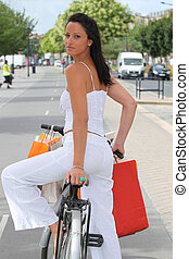Woman with store bags riding a bike in the city